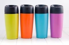 Colora canecas da garrafa térmica na tabela de madeira branca Imagem de Stock