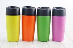 Colora canecas da garrafa térmica na tabela de madeira branca Imagens de Stock Royalty Free