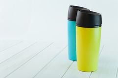 Colora canecas da garrafa térmica na tabela de madeira branca Fotos de Stock