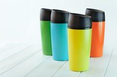 Colora canecas da garrafa térmica na tabela de madeira branca Imagens de Stock