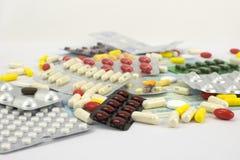 Colora comprimidos nos sacos em uma superfície branca Fotografia de Stock Royalty Free