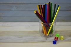 Colora dos dados acrílicos coloridos de vidro do frasco dos lápis o fundo rústico de madeira fotos de stock