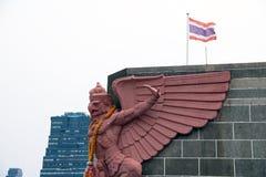 Colora a estátua de Garuda na parte superior da construção e da bandeira nacional tailandesa Fotos de Stock Royalty Free