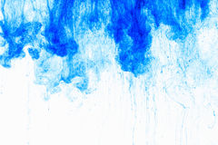 Colora a gota da tinta na água, fotografada no movimento, rodando Icloud azul da pintura no fundo branco Foto de Stock Royalty Free