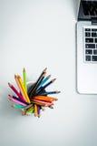 Colora lápis em uma caneca branca e em um portátil Fotos de Stock Royalty Free