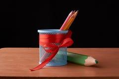 colora lápis na lata de lata com os lápis verdes grandes na tabela de madeira no fundo preto Fotografia de Stock