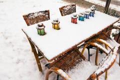 Colora lâmpadas na tabela do café da rua no inverno da neve Imagem de Stock