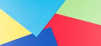 Colora o fundo liso da composição da geometria dos papéis com tons amarelos, verdes, vermelhos e azuis Fotografia de Stock
