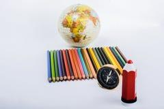 Colora o lápis com compasso, pena e um globo Imagens de Stock