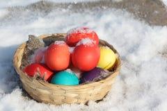 Colora ovos da páscoa em uma cesta de madeira na neve Fotos de Stock