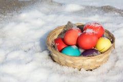 Colora ovos da páscoa em uma cesta de madeira na neve Imagens de Stock Royalty Free