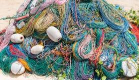 Colora a rede de pesca, flutuadores, corda de nylon no banco Imagens de Stock
