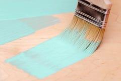 Coloración de la superficie de madera de la pintura de la turquesa usando una brocha Foto de archivo libre de regalías