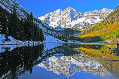A Colorado Autumn at the Maroon Bells. The snow capped peaks of the Maroon Bells reflects in Marron Lake near Aspen Colorado Stock Photo