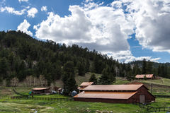 Colorado Farm Ranch in Mountains. Brown wooden barn building on a ranch farm in the colorado mountains with forest blue sky and clouds Stock Photography