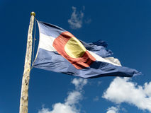 Colorado Flag against Bright, Blue Sky. Colorado flag on rustic timber pole flying briskly against bright blue sky with a few white clouds stock image