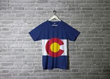 Colorado flag on shirt and hanging on the wall with brick pattern wallpaper. The states of America stock image