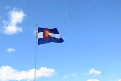 Colorado Flag waving in the wind against a blue cloudy sky. The Colorado flag waves proudly against a blue sky with a few clouds in the distance royalty free stock images