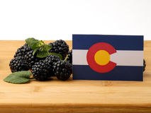 Colorado flag on a wooden panel with blackberries isolated on a. White background royalty free stock images