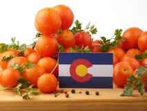 Colorado-Flagge auf einer Holzverkleidung mit den Tomaten lokalisiert auf einem Whit stockfotos