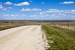 Colorado High Plains Farm Road. Gravel road takes a crooked path over rolling hills in eastern Colorado under scattered clouds Royalty Free Stock Photos