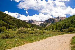 Colorado Mountains and Clouds. Beautiful Colorado mountains and high white clouds on a dirt road near the end of the valley Royalty Free Stock Images