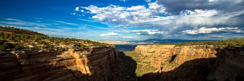 Panoramic view of long, deep canyon walls in Colorado National Monument near the towns of Grand Junction and Fruita. Panorama of sunset light on the long, steep royalty free stock photography