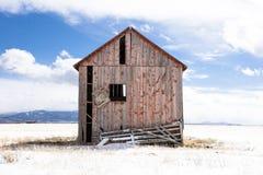 Colorado röd ladugård i snöfält arkivfoton