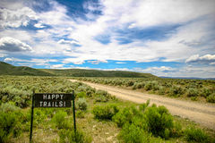 Colorado ranch landscape with a dirt road running through it and a sign with the words Happy Trails. Stock Photography