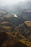The Colorado River cuts through the Grand Canyon. The Colorado River shines through a hazy Grand Canyon stock photography