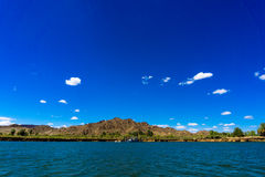 Colorado river and mountains and dredging barge under blue sky. In Yuma Arizona Royalty Free Stock Photos