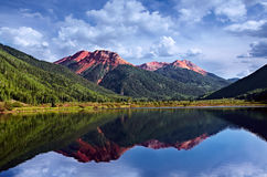 Colorado San Juan Skyway Red Iron Peaks Lake. Colorado San Juan Skyway, Red Iron Peaks Reflecting In A Crystal Clear High Mountain Lake With Conifer Pines and Stock Photo