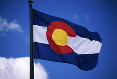 Colorado State Flag. This is the Colorado State Flag, waving in the wind situated on a flag pole. It is set against a blue sky. At the center of the flag is a royalty free stock photos