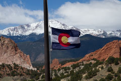 Colorado State Flag with Pikes Peak and Garden of the Gods in th. E background on a spring day royalty free stock image