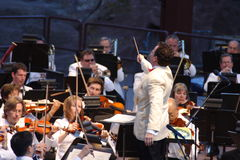 Colorado Symphony Orchestra. Associate Conducter, Scott O'Neil, conducts the Colorado Symphony Orchestra while performing at Red Rocks Amphitheatre in Morrison Stock Photos