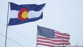 Colorado and United States Flags. The Colorado flag and United States of America Flag, in wind and snow. HD 1080p Hand-held footage clip stock video footage