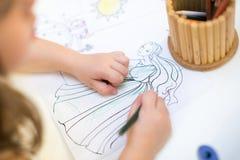 Colorante de la chica joven en libro de colorear los niños dibujan la fiesta de cumpleaños foto de archivo libre de regalías
