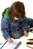 Colorante del muchacho en un cuaderno Imagen de archivo libre de regalías