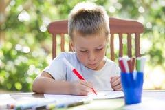 Colorante del niño pequeño afuera Fotos de archivo