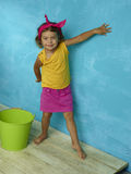 Colorbaby. The little girl in a bright-colored clothing with a new green bucket on the background of bright blue walls Stock Photography