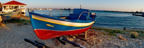 Colordul boat in a beach. A picture of a colorful boat and a small pier house in the distance,in a beach,in a small town in Greece,Moudania in a summer day Stock Photos