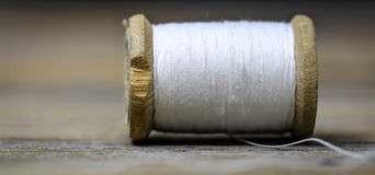 Colore bianco del filato cucirino con un ago fotografia stock