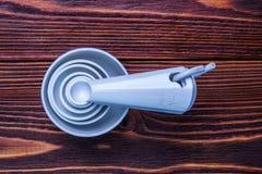 Colore bianco di plastica stabilito di misurazione dei cucchiai e delle tazze della tavola su woode fotografia stock libera da diritti