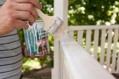 Colore bianco di verniciatura della spazzola della tenuta della mano sul primo piano di legno del gazebo Fotografia Stock
