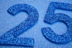 Colore del blu di numero venticinque sopra un fondo blu anniversario Immagine Stock