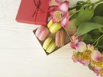 Colore di Macaron in una scatola sul fiore di legno bianco di alstroemeria del fondo del forno Fotografia Stock