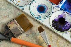 Colore di manifesto, spazzole e tavolozza di plastica con le pitture variopinte fotografie stock libere da diritti
