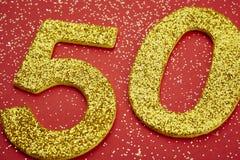 Colore dorato di numero cinquanta sopra un fondo rosso anniversario Immagini Stock