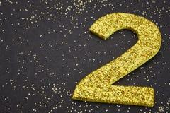 Colore dorato di numero due sopra un fondo nero anniversario Immagini Stock Libere da Diritti