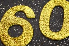 Colore dorato di numero settanta sopra un fondo nero anniversario Immagine Stock